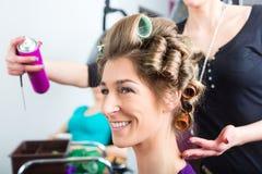 Hairdresser - hair stylist curling hairs. A female customer gets a haircut stock photos