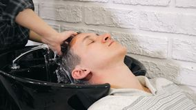 Hairdresser Hands Washing Dark male Hair Under Running Water In The Barbershop. Closeup stock photos