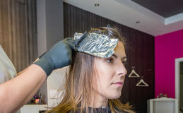 Hairdresser hands wrapping woman hair with Stock Photos