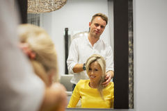 Hairdresser with his client in hair salon Royalty Free Stock Photos