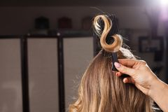 Hairdresser holding a hair curl with a comb royalty free stock photography