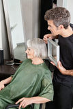 Hairdresser Holding Mirror Behind Senior Woman Royalty Free Stock Photos
