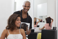 Hairdresser holding a mirror behind young woman Royalty Free Stock Images