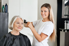 Hairdresser Ironing Customer's Hair Stock Photos