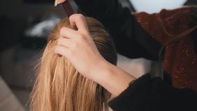 Hairdresser make-up artist hairstyle Caucasian model blonde. Uses hairbrush and varnish. Knotting the tail of the hair. Close-up, make-up business woman. Slow stock video