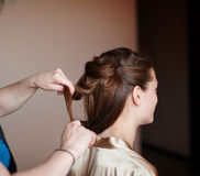 Hairdresser makes the bride hairstyle in wedding morning Stock Photos