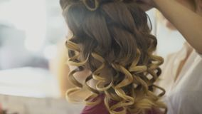 Hairdresser makes curls for woman and artist applies makeup on face. Stylist does hairstyle diligently while visagist puts cosmetic colors on skin, holding stock footage