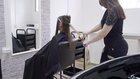 Hairdresser makes hair lamination in a beauty salon for a girl with brunette hair stock video footage