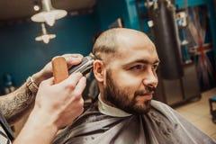 Hairdresser makes hair short man stock photo