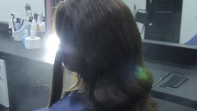 Hairdresser makes hair styling at the beauty salon stock video footage