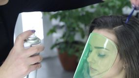 Hairdresser makes hair styling at the beauty salon. The model is covering her face a protective mask stock video footage