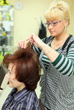 Hairdresser makes hair styling for woman. Hairdresser makes hair styling for women by rake-comb in beauty salon Royalty Free Stock Photo