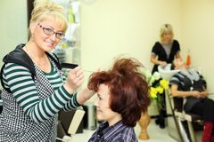 Hairdresser makes hair styling for woman. Smiling hairdresser makes hair styling for women by rake-comb and looks at camera in beauty salon; focus on barber Stock Images