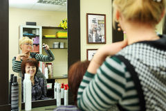Hairdresser makes hair styling for woman Royalty Free Stock Image