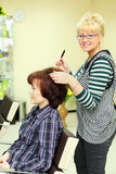 Hairdresser makes hair styling for woman Stock Image