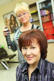 Hairdresser makes hair styling for woman Royalty Free Stock Photo