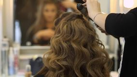 Hairdresser makes hairdress beautiful girl in a beauty salon stock footage