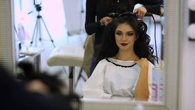 Hairdresser makes hairdress beautiful girl in a beauty salon stock video