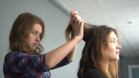 Hairdresser makes hairdress beautiful girl in a beauty salon stock video footage