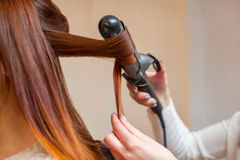Hairdresser makes hairstyle girl with long red hair in a beauty salon. Royalty Free Stock Photo