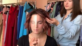 Hairdresser makes styling. And makeup for pretty woman model stock video footage