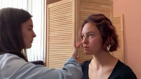 Hairdresser makes styling. And makeup for pretty woman model. Fast motion stock footage