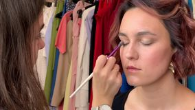 Hairdresser makes styling. And makeup for pretty woman model stock footage