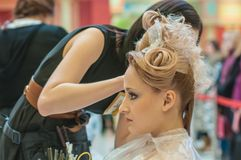 Hairdresser makes the wedding hairstyle. Stock Image