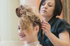 Hairdresser makes the wedding hairstyle. Royalty Free Stock Photo
