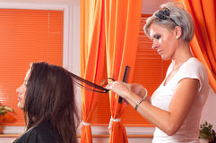 Hairdresser making cutting long hair of beautiful teenage girl Royalty Free Stock Image