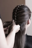 Hairdresser making a dutch braid. Close up of hands stock photo