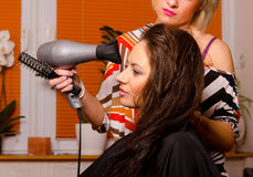 Hairdresser making hair of beautiful girl Royalty Free Stock Images