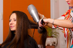 Hairdresser making hair of beautiful girl Royalty Free Stock Photography