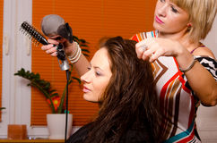 Hairdresser making hair of beautiful happy girl royalty free stock photo