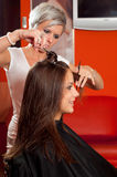 Hairdresser making hair of beautiful smiling teenage girl Royalty Free Stock Photography