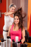 Hairdresser making hair of beautiful smiling teenage girl Stock Photography