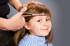 Hairdresser making a hair style to cute little girl Stock Images