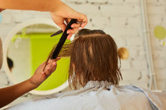 Hairdresser making a hair style to cute little girl. Royalty Free Stock Photos