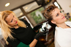 Hairdresser making hair treatment to a customer in salon Stock Photography