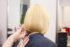A hairdresser making haircut for a blonde female Royalty Free Stock Images