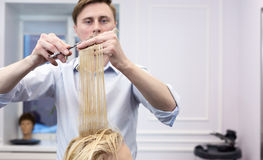 A hairdresser making haircut for a blonde female client Royalty Free Stock Image
