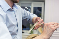 A hairdresser making haircut for a blonde female client Royalty Free Stock Photo