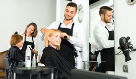 Hairdresser making haircut for customer Royalty Free Stock Photo