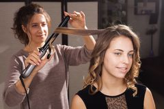 Hairdresser making a hairdo with waves to a model stock photography