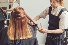 Hairdresser making a hairstyle for client stock image