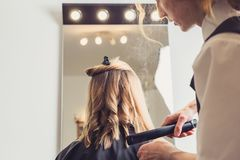Hairdresser making a hairstyle for client stock photography
