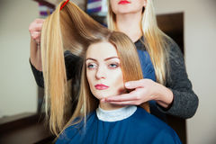 Hairdresser making hairstyle with hairbrush. Stock Images