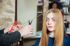 Hairdresser making hairstyle with scissors. Stock Photo