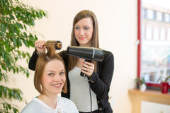 Hairdresser making locks with barrel brush and blow-dryer Stock Image