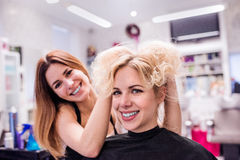 Hairdresser making a new haircut to her handsome client Royalty Free Stock Images